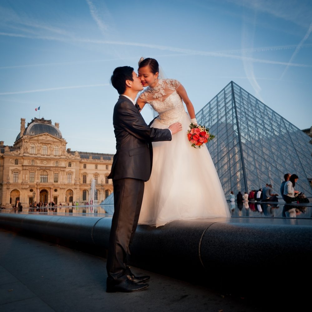 Paris Photographer bride and groom kissing Pyramide Louvre