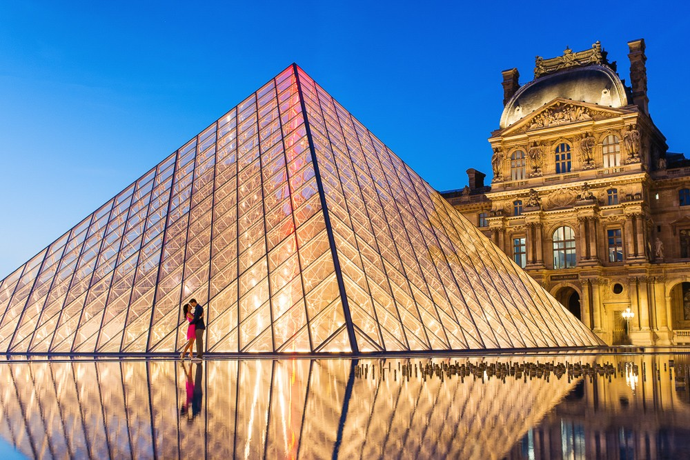 Paris photographer night photo at Louvre Museum with couple on honeymoon