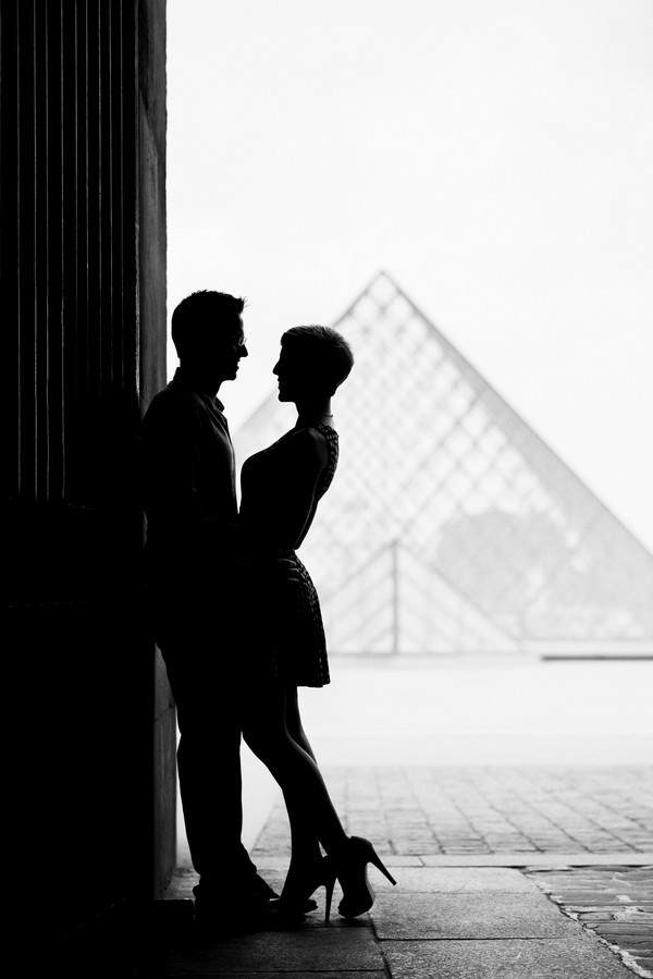 Silhouette picture Louvre Pyramid with couple after proposing in Paris