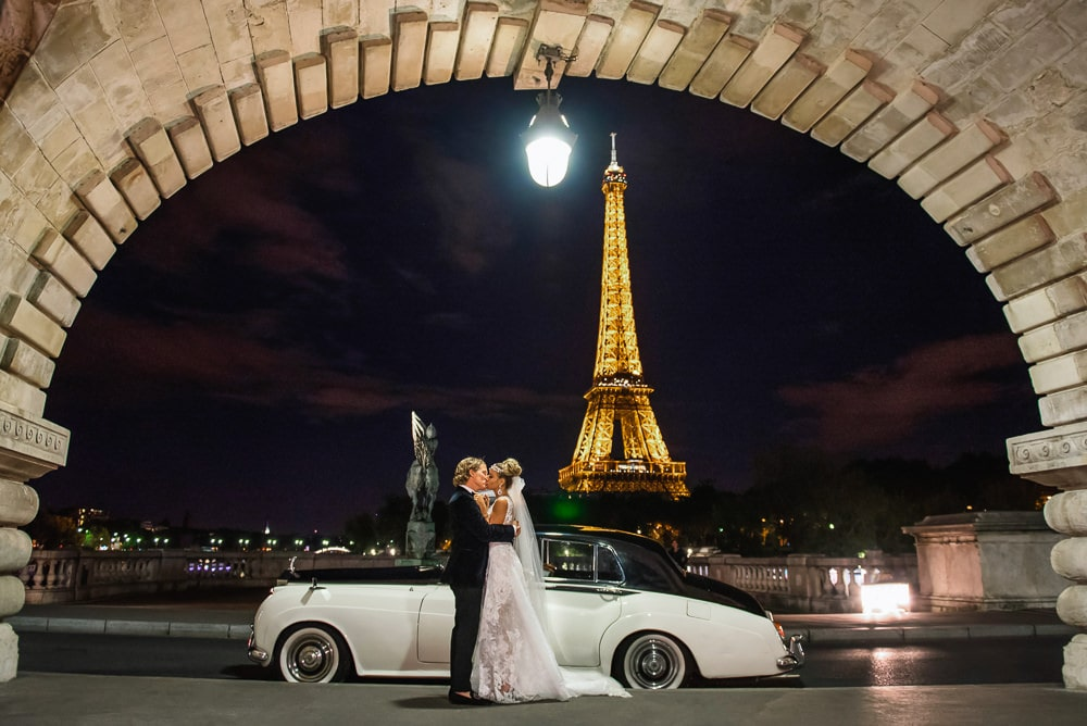 Bride and groom kissing next to vintage Rolls Royce in front of the Eiffel Tower at night