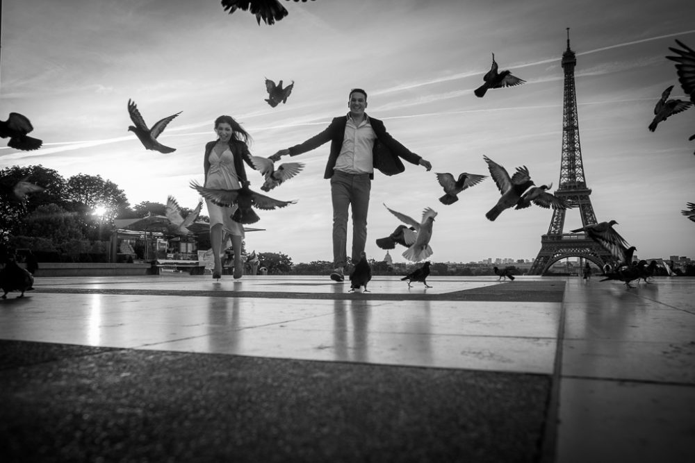 engagement photos in paris couple chasing pigeons at Eiffel Tower