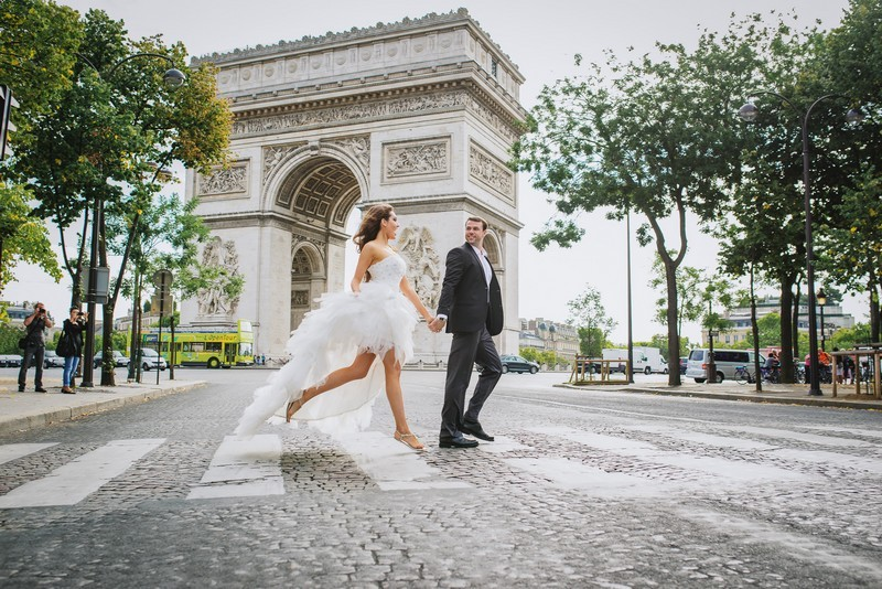 Happy bride and groom wrossing street at Arc de Triomphe in Paris