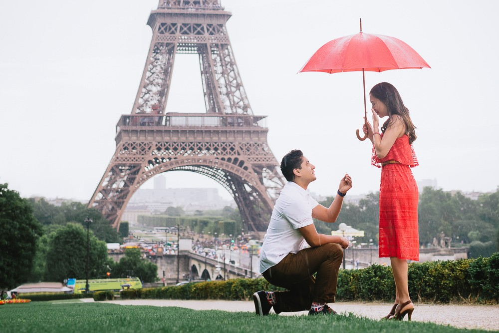 Paris photographer man on one knee proposing to his girlfriend in the rain