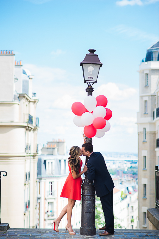 Couple kissing under red balloons in Montmarte