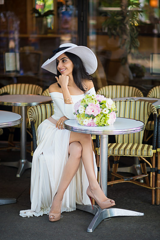 Portrait of a beautiful girl wearing a hat and smiling in a Parisian café