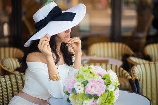 Portrait of a beautiful girl wearing a hat in a Parisian café