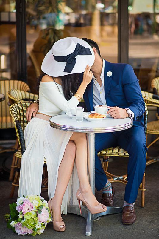 A couple kissing under a hat in Paris