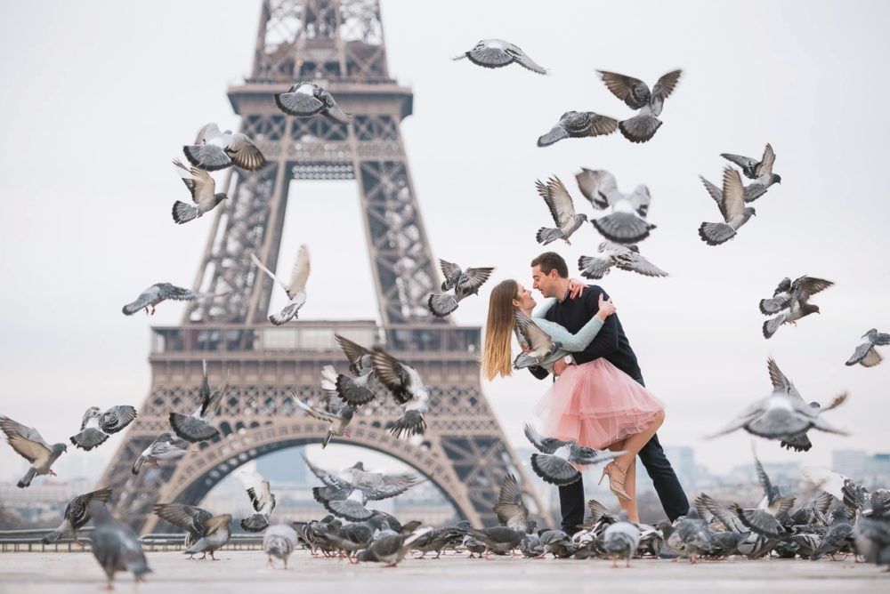 Paris photographer Ioana – couple surrounded by birds at Eiffel Tower