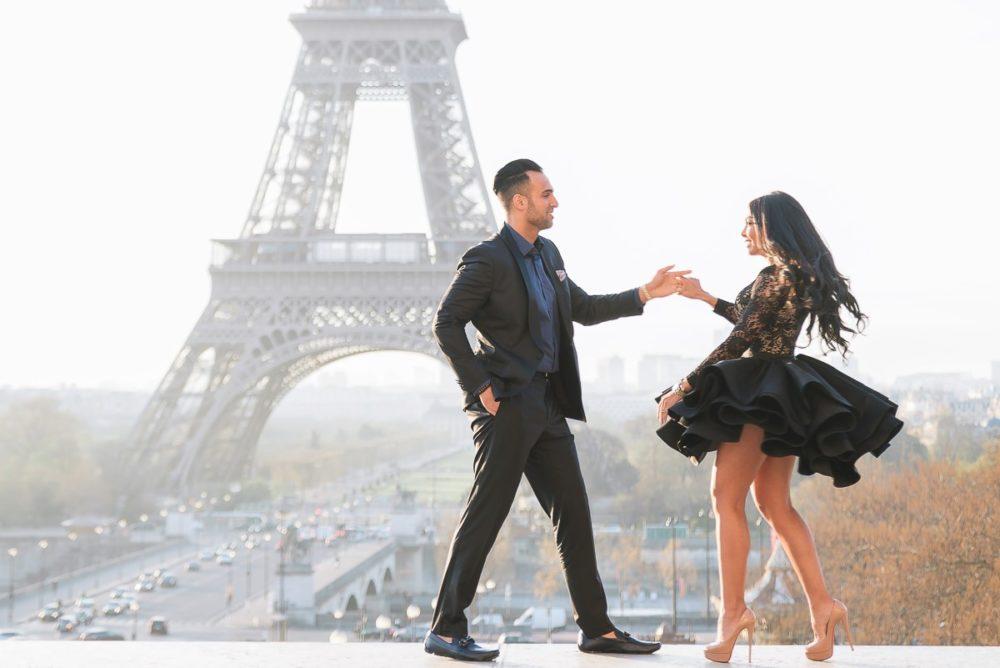 Paris photographer Ioana – elegant couple dancing in front of the Eiffel Tower in Michael Costello designer dress