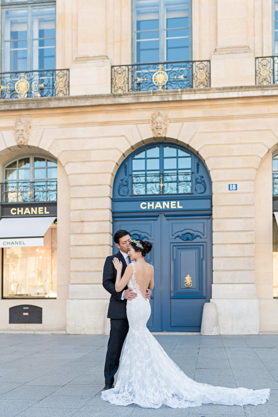 pre wedding photo bride and groom kissing in place vendome in front of chanel store