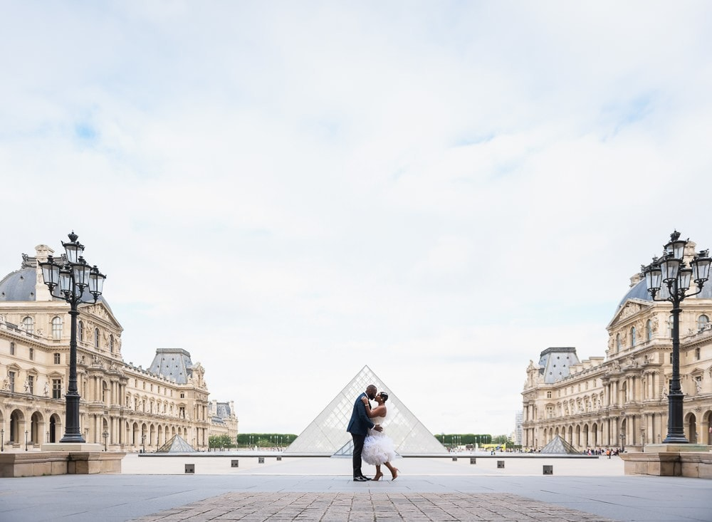 Couples shoot ideas - Black bride and groom kissing in the courtyard of the Louvre Museum