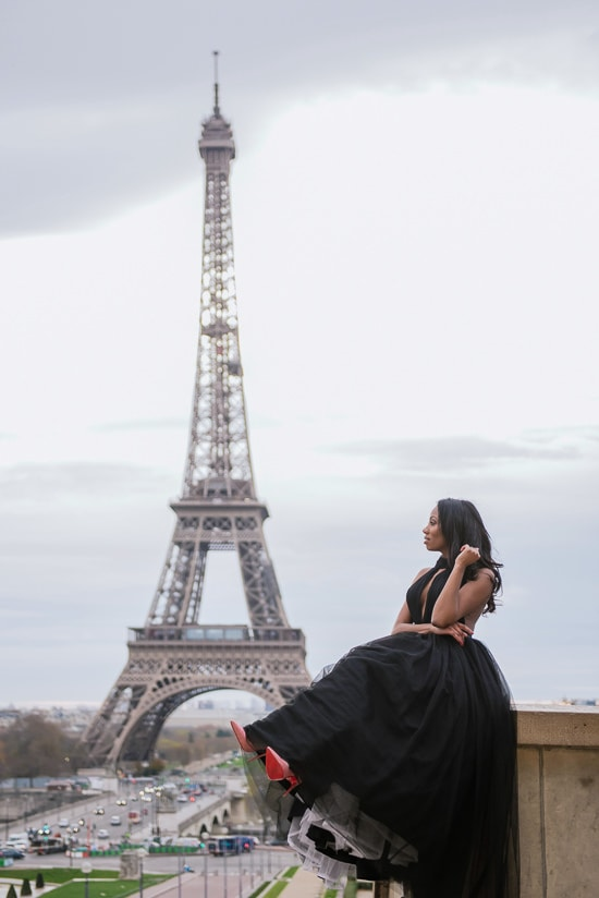 Cute girl wearing Louboutin stilettos posing in front of the Eiffel Tower