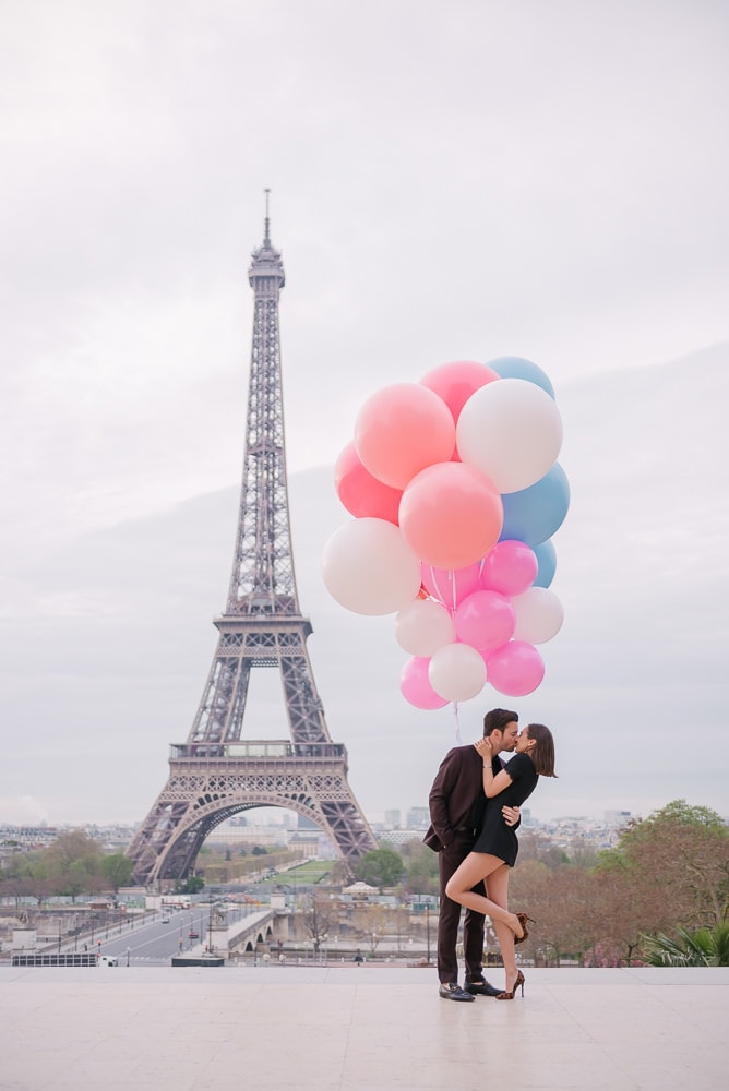 Crazy couples pictures  Young couple kissing underneath huge and colorful balloons in Paris