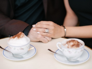 Cute close-up of holding hands and showing engagement ring