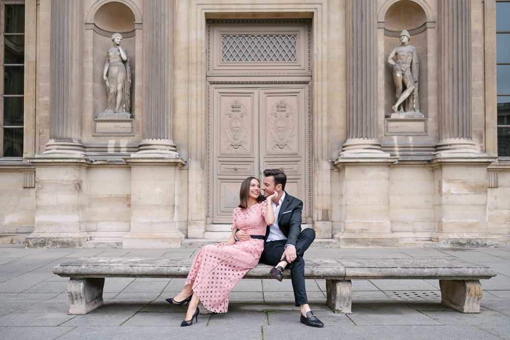 Engagement picture dresses - Girl in pink long dress being hugged by her fiancé in front of old door at the Louvre Museul in Paris