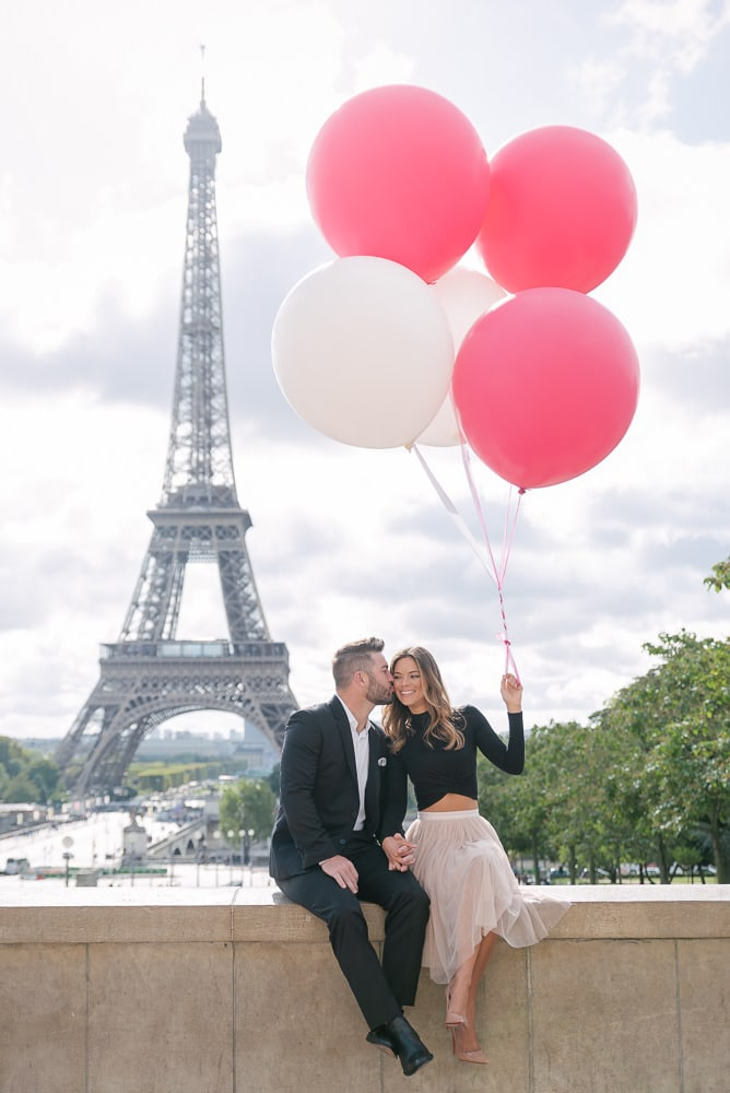 Girl holding big colorful balloons and fiancé kissing her on the cheek