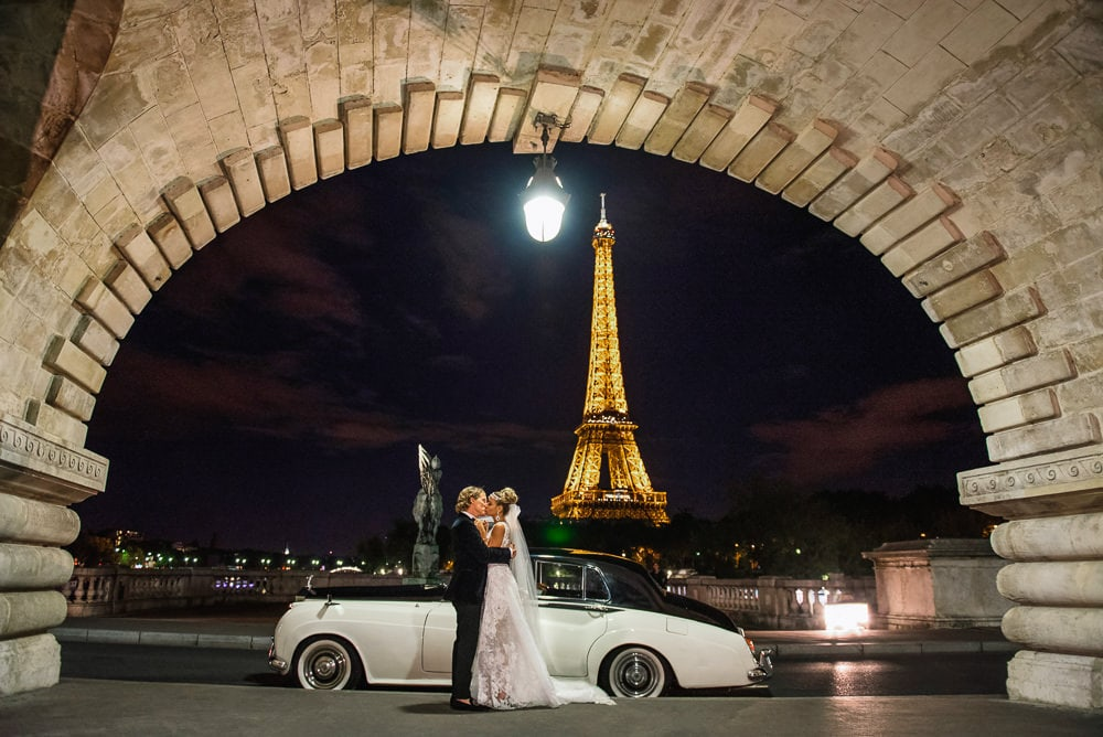 best photography spots in Paris bride and groom kissing in front of white vintage rolls royce on the bir hakeim bridge