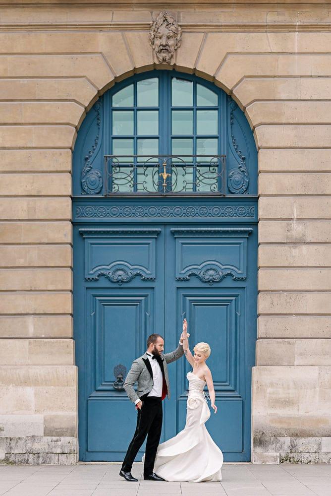 best photography spots in Paris with bride and groom dancing in front of blue door