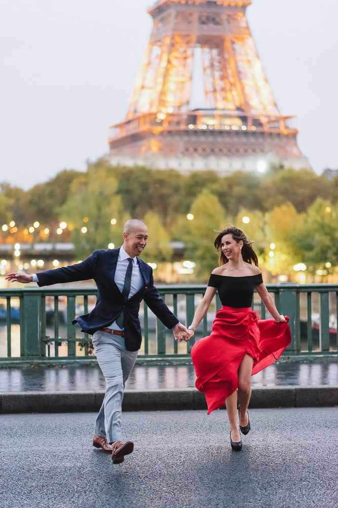 best places to take pictures in paris cute couple running across the street on the pont bir hakeim