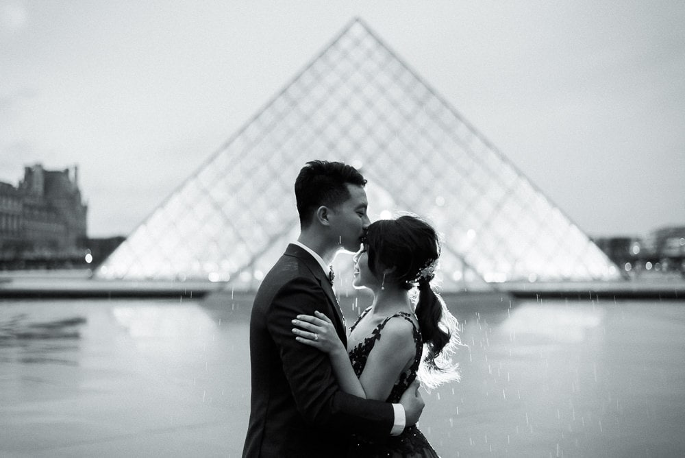 most romantic spots in paris – louvre museum cute asian couple kissing in the rain
