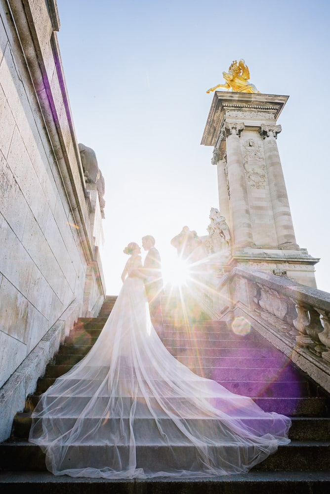 Paris Pre wedding photographer - Bride and groom kissing on the Alexander 3 bridge with the sun in the back