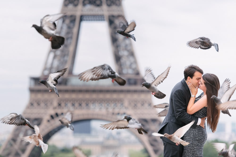 Paris engagement photographer capturing newly engaged couples kissing among flying birds at the Eiffel Tower