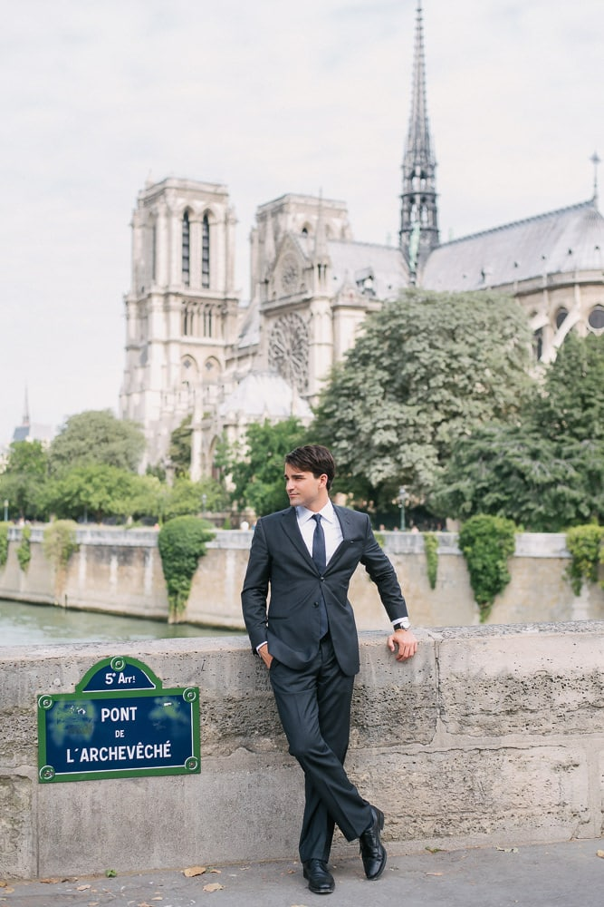 Portrait of a young man dressed elegantly in front of the Notre Dame cathedral