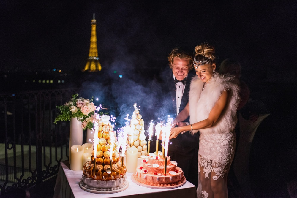Bride and groom cutting La Durée wedding cake on the rooftop of the peninsula paris