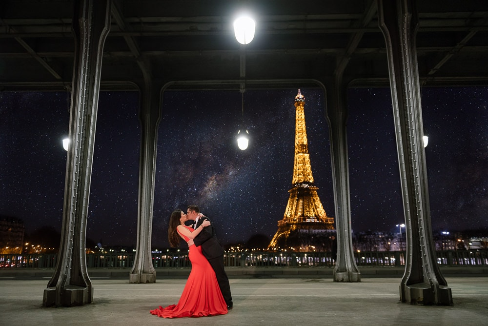 Pre wedding couple kissing at the Eiffel Tower by night where the milky way is showing